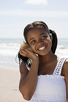 Girl listening to a shell on a beach