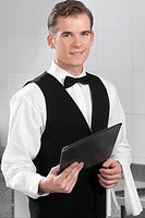 Portrait of a waiter holding a menu in a restaurant
