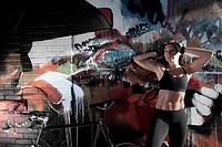 Woman standing with a bicycle in front of a graffiti covered wall
