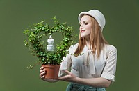 Close_up of a woman holding a flower pot with a light bulb