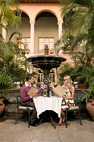 Couple holding menu cards and toasting with wine, Biltmore Hotel, Coral Gables, Florida, USA