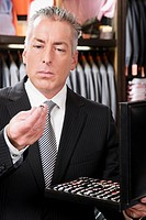 Businessman selecting cuff links in a clothing store