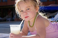 Portrait of a baby girl drinking juice with a straw