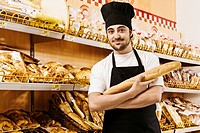 Salesman holding a loaf of bread in a supermarket