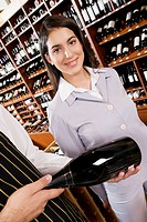 Sales clerk showing a wine bottle to a businesswoman
