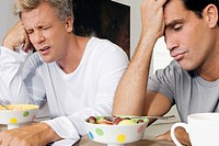Men frowning at bowls of cereal and fruits