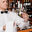 Waiter cleaning a wine glass in a bar