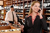 Businesswoman talking on a mobile phone and holding a wine bottle