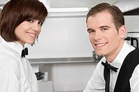 Portrait of a male and a female waiters smiling