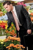 Businessman choosing flowers in a florist´s shop