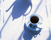 Cup of coffee and shadow of a teapot on table