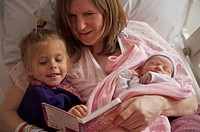 Mother with daughter and newborn girl in hospital bed reading a book