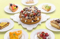 Pieces of tart around tart with cream puffs and strawberry, colored background