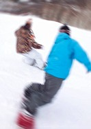 People snowboarding down mountain