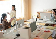 Woman giving co_workers coffee in home office