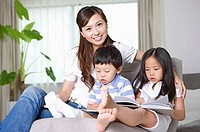Family, mother together with two children at home, son and daughter reading