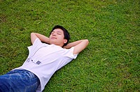 Young boy lying on the lawn with eyes closed and listening music, Teenager