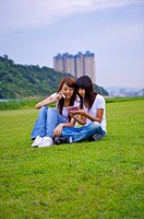 Two girls sitting on the lawn together, Teenager