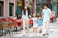 Young family with two children holding hands together and walking on the road, Family, Leisure Activities