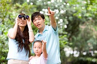 Young family with little girl pointing and looking up with a telescope, Family, Leisure Activities