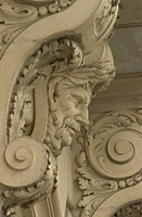 Stone carvings under a balcony of a building in Paris , France
