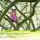 Woman sitting on tree branch