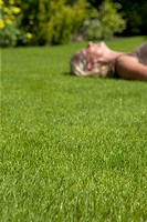 Lawn with relaxing woman in background