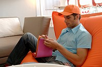 Young man with an orange cap sitting on a settee and is choosing a color