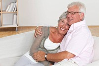 Senior couple hugging on sofa