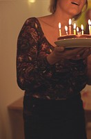 Woman holding a Birthday Cake cropped (thumbnail)