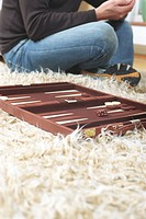 Man sitting cross_leged on the Floor and Backgammon Board laying on a Carpet
