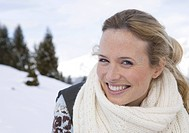 Happy woman wearing scarf in winter landscape