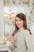 young woman with glass of bubbly in bed