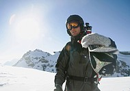 Skier carrying skis on shoulder