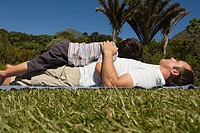 Father and son resting on lawn