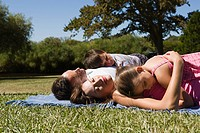 Family lying and resting together on picnic blanket in park