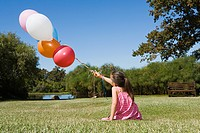 Little girls sitting on grass holding balloons