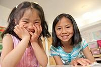 portrait of happy school friends sitting at desk in classroom
