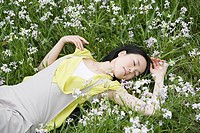 Young woman lying in field of flowers