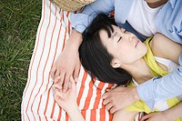 Young couple sleeping on blanket