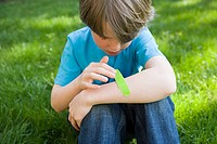 Boy putting plaster on arm
