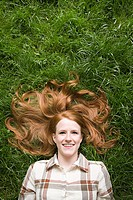 Ginger haired woman lying on grass