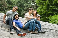 Two young couples sitting on rocks