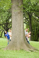 Friends hiding behind a tree