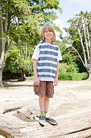 Boy standing on log