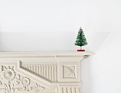 Miniature christmas tree on mantlepiece