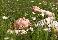 woman lying in grass with spring flowers