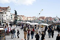 Tourists at a seaside promenade with souvenir stalls, Rider Memorial in the background, Venice, Italy