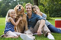 Family in the park with golden retriever