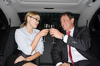 Businesspeople toasting in a car